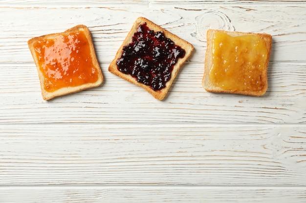木製の背景、上面においしいジャムとトースト