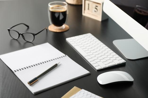 Рабочее место с компьютером, очки и календарь на черном деревянном столе, крупным планом