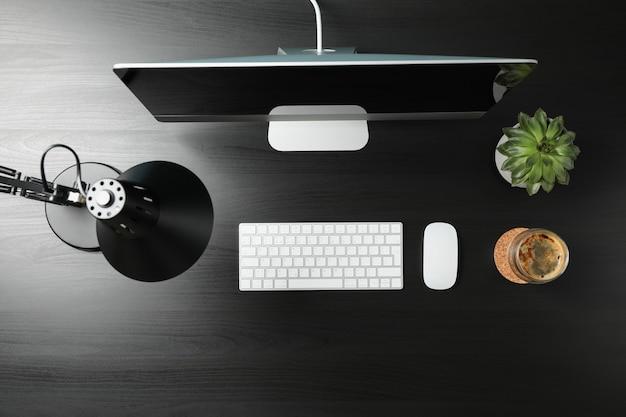 Плоская планировка с компьютером, заводом и стаканом кофе на черном деревянном столе, вид сверху