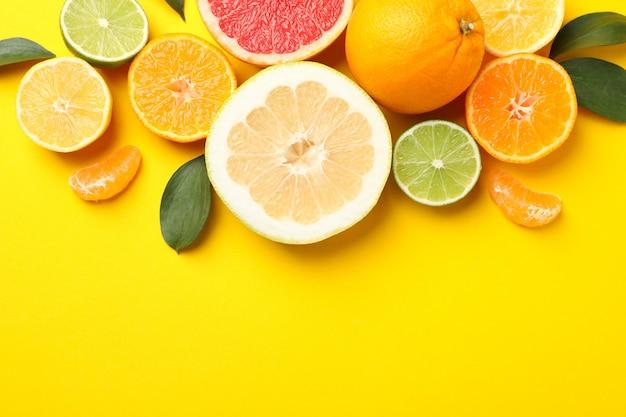 柑橘系の果物と黄色の背景、上面に葉