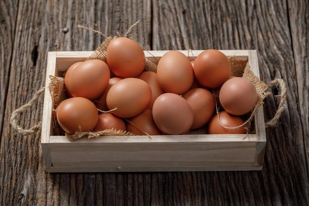 Коричневые яйца в деревянной коробке на деревянный стол, куриное яйцо