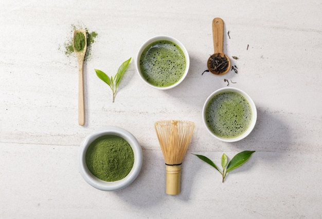Органический порошок зеленого чая маття в миске с проволочным венчиком и листом зеленого чая на белом каменном столе