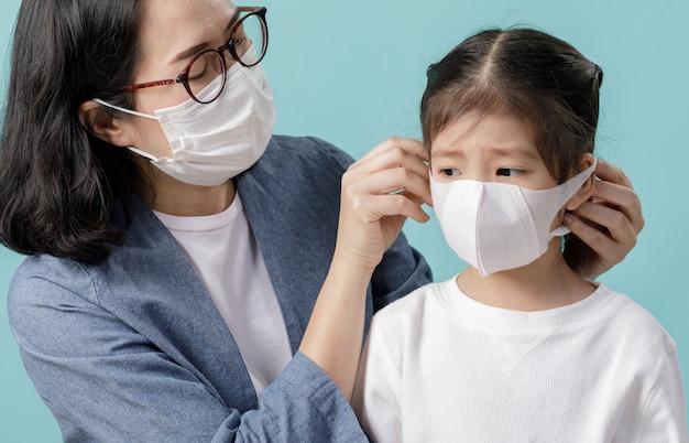 自分自身を保護するために医療用フェイスマスクを身に着けているママとアジアの小さな子供女の子