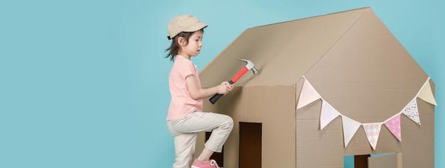 Азиатская девочка маленького ребенка, строящая ее картонный дом, изолированный на синем длинном баннере с копией, делает интервалы для вашего текста, творческого дома с концепцией семьи