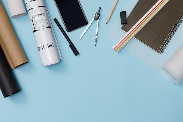 Творческая планировка архитекторов синего стола с рулонными чертежами, архитектурного плана проекта, инженерных инструментов, канцелярских принадлежностей, изолированных на синей стене, рабочей области для дизайнерской концепции