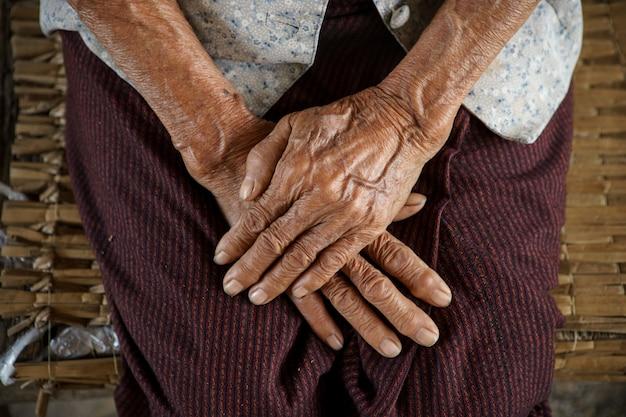 アジアの祖母の手を握る
