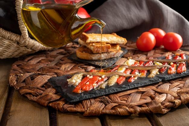 エスカリバダは、素朴な木製のテーブルの枝編み細工品バスケットにバージンオリーブオイルと野菜で洗い流されました。