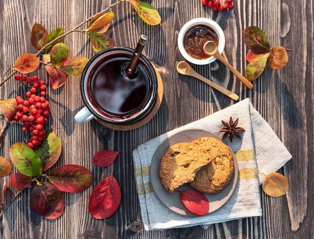 Красная чашка чая с палочкой корицы, вареньем и печеньем на деревянном столе осеннее настроение