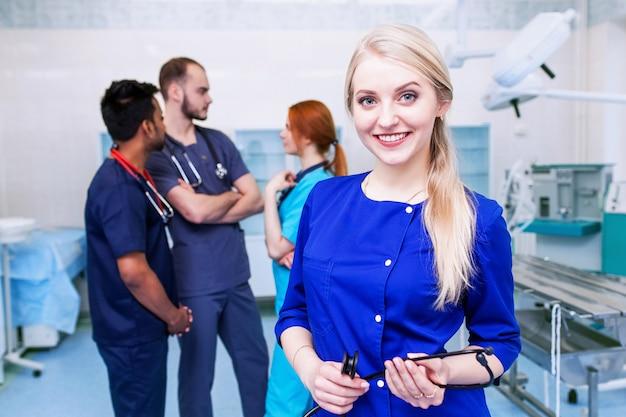 Молодая блондинка хирург, улыбаясь с командой студентов-медиков смешанной расы в университете
