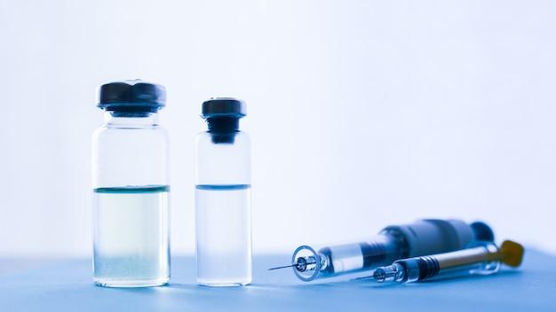ウィンドウの背景を持つ青いガラステーブルの上の薬と注射器のバイアル