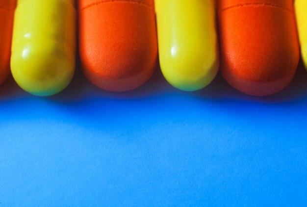 白い選択と集中にマクロカラフルな錠剤。青色の背景にタブレット。写真をクローズアップ