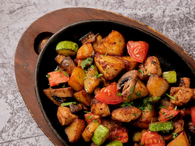 素朴なスタイルの鍋でハーブと野菜のおいしいオーブン焼きジャガイモ。ポテトフライ、レッドチェリートマト、ズッキーニ、タマネギ