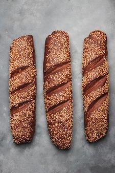 灰色の石の背景にゴマと全粒小麦のパン。コピースペースの平面図です。フラットレイ。