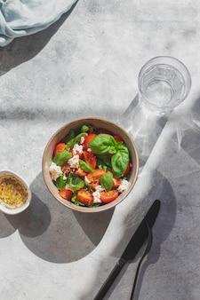 Зеленая летняя салатница с помидорами, базиликом и сыром моцарелла и оливковым маслом