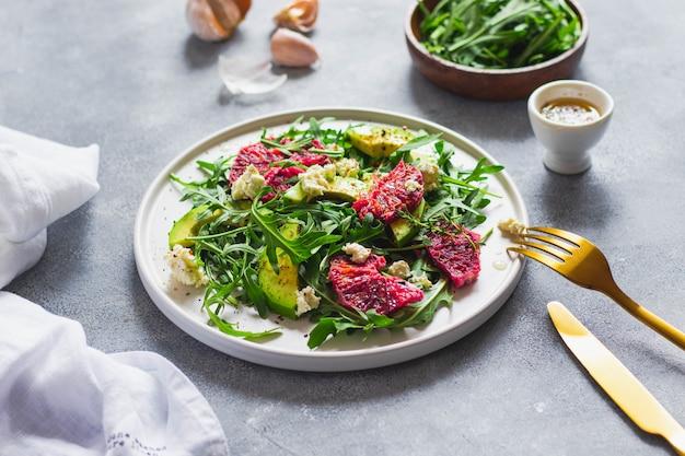 ルッコラ、ブラッドオレンジ、アボカド、カッテージチーズのグリーンサラダ。青い石の壁に金のフォークとナイフ、白いリネンナプキンで焼かれた。健康的な食事のコンセプトです。上面図
