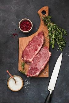木製のまな板、ローズマリー、海の塩、ナイフ、黒い石の壁にピンクのコショウで新鮮な生の牛肉ステーキブラックアンガス。フラット横たわっていた。