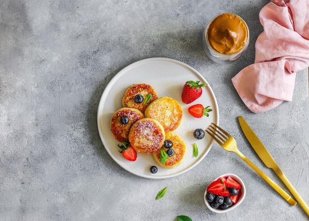 コーヒーと健康的な朝食のコンセプトです。灰色の壁にフォークとナイフで焼かれた白いセラミックプレートにイチゴ、ブルーベリー、ミントの葉とチーズのパンケーキ。カルシウムビタミン食品。