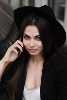 黒い帽子をかぶって携帯電話を使う女性