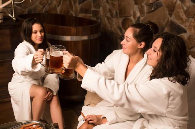 バスローブで幸せな若い白人女性はサウナでプールの隣に座って、冷たいビールを飲みます。
