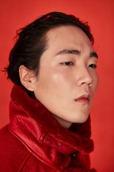 Азиатский мужчина в красной одежде на красном пространстве