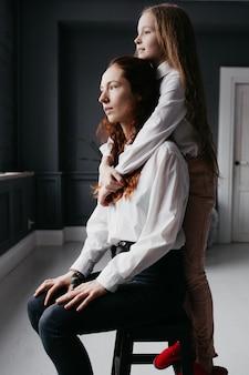 Молодые и взрослые сестры обнимаются на чердаке, представляя дружбу, доверие, сходство