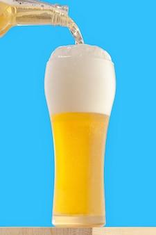 Высокий стакан с легким охлажденным пивом. пиво наливают в стакан.