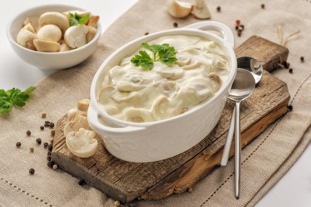 キノコの濃厚なクリーミーなソースが木の板の上に立つ、白い鍋の深い鍋