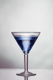 Стакан синего алкогольного напитка на белой стене