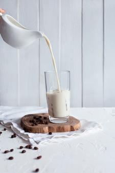 氷でグラスに牛乳を注ぐ