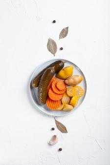 発酵キュウリ、ニンジン、スカッシュ、白いテーブルの上の食材