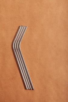 Экологичные металлические коктейль соломинки на фоне крафт-бумаги. вид сверху