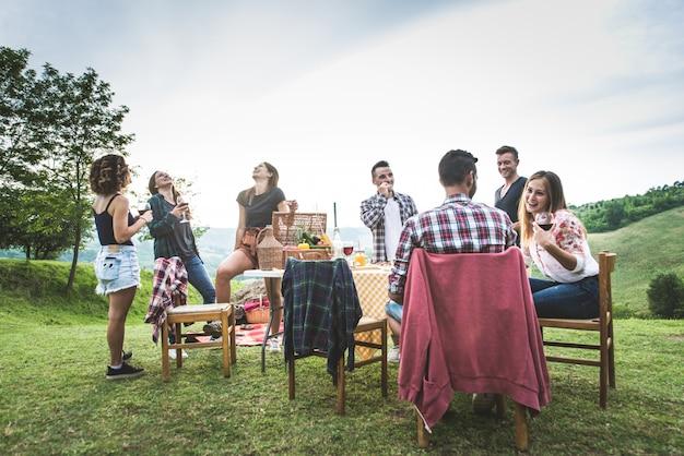 Группа друзей едят на природе