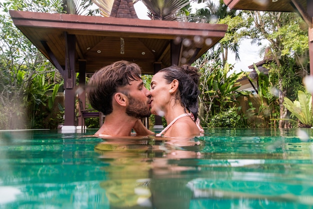 スイミングプール付きの美しいヴィラで恋人のカップル