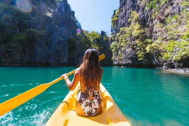 Женщина на байдарках в малой лагуне в эль-нидо, палаван, филиппины - блогер-путешественник, изучающий лучшие места юго-восточной азии