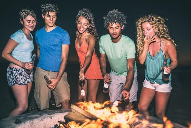 Группа друзей, веселиться на пляже, делая костер