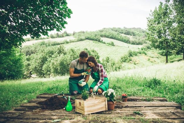 Пара отдыхает и сажает цветы во дворе своего загородного дома