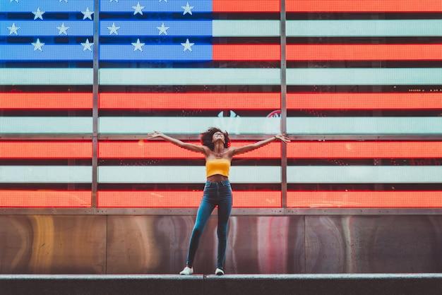 マンハッタンのタイムスクエアを歩く美しい少女。ニューヨークに関するライフスタイルの概念