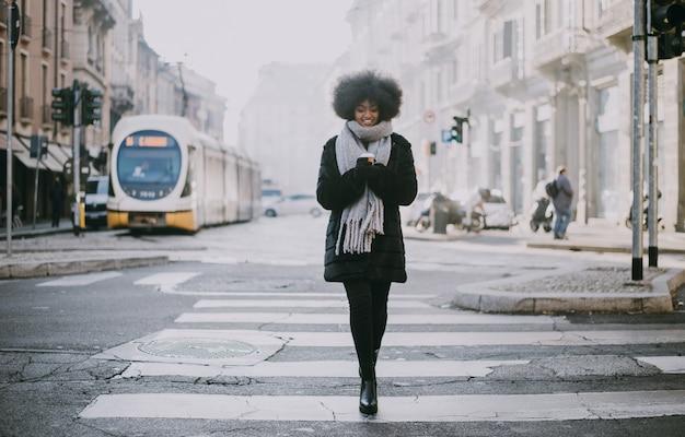 通りを歩いてアフロのヘアカットで美しい少女