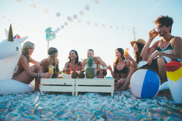 日没時にビーチでパーティーをする友人のグループ