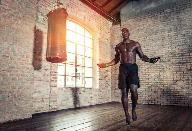 Черный боец усердно тренируется в своем спортзале