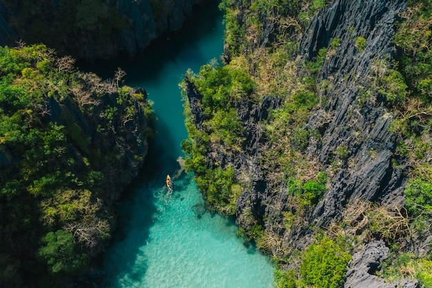 エルニドの秘密のラグーン。透明な水とカヤックで時間を楽しんでいるカップル。旅行と自然についての概念