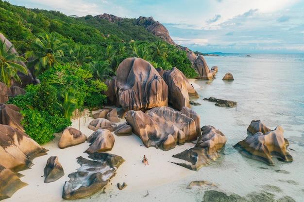 セイシェルの「ラディーグ」島。花崗岩の石とジャングルのあるシルバービーチ。休暇を楽しんで、ビーチでリラックスした男。空撮
