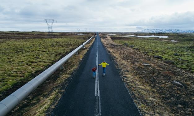 アイスランドの道路上のスケートボーダーのカップル