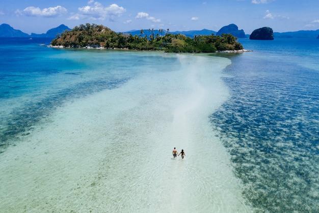 ビーチでの時間を楽しんでいます。熱帯のジャングルで、白い砂の上を歩く人。旅行と自然についての概念
