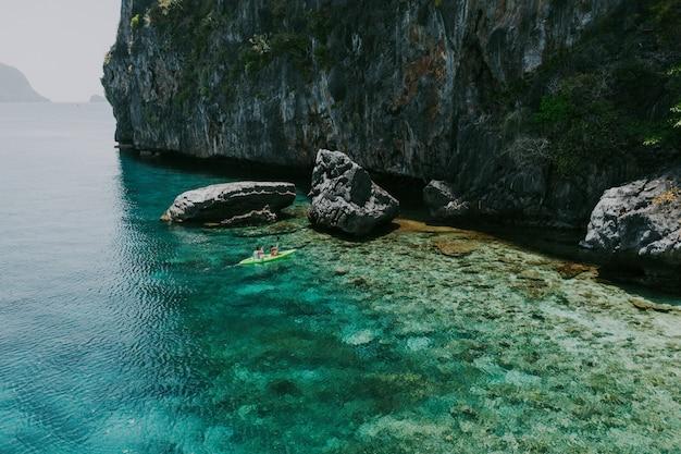 コロンのビーチの前でカヤックを楽しむカップル。夏、ライフスタイル、放浪旅行、自然についての概念