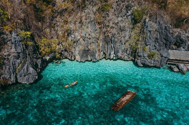 岩と漁師の家の間のツインラグーンでカヤックし、風景を楽しんでいます。フィリピン旅行に関する概念