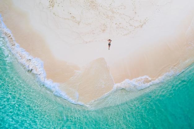 空からのダク島の眺め。ビーチで日光浴を取ってリラックスした男。美しいシーンの上にドローンで撮影したショット。旅行、自然、海洋の風景についての概念