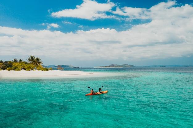 フィリピンの美しい熱帯の島で過ごすカップル。休暇とライフスタイルについての概念。カヤックとアクティビティを行う