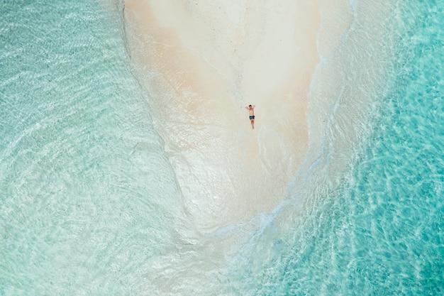 空からの裸の島の眺め。ビーチで日光浴を取ってリラックスした男。美しいシーンの上にドローンで撮影したショット。旅行、自然、海洋の風景についての概念