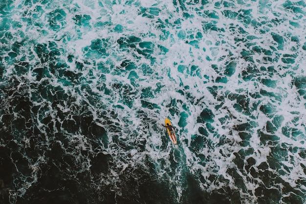 日没時にサーフィンをしているサーファーの空中ショット。ドローンで提供される写真。自然とスポーツについての概念